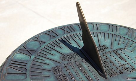 Old fashioned brass sun dial with shadow indicating time of day